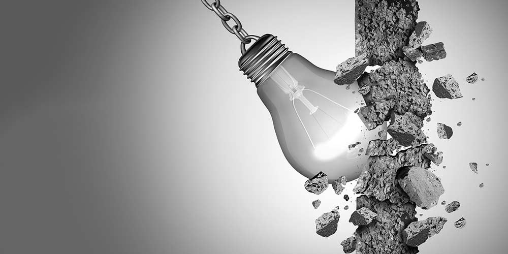 Lightbulb breaking through wall to symbolize the breakthrough creative moment in a brand strategy